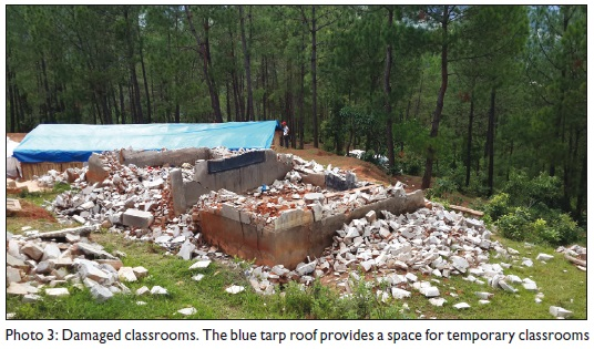 Damaged classrooms. The blue tarp roof provides a space for temporary classrooms